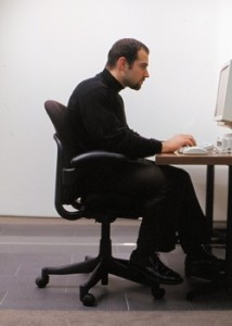 A man in front of his PC with his cervical spine hyperextended